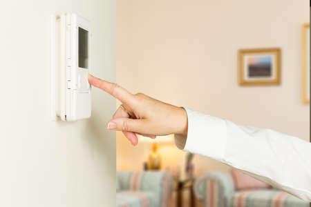 woonwijk: Blanke vrouw de hand te drukken-knop op een moderne elektronische thermostaat timer op de muur van een modern huis met focus op het scherm en de vingers van de vrouw