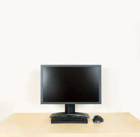 Plain light colored wooden desk with computer monitor and keyboard to suggest calm, organization and meditation at work or in home office