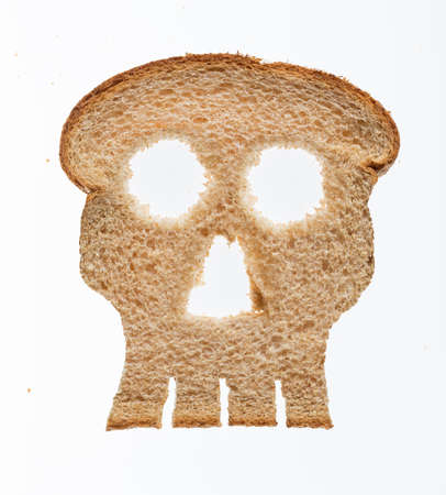 Skull shaped piece of bread cut from whole wheat loaf to illustrate danger from gluten in wheat products photo