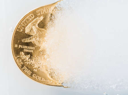 ounce: Gold eagle one ounce coin emerging from a frozen ice block to illustrate concept of gold coming out of deep freeze, pricing going to rise