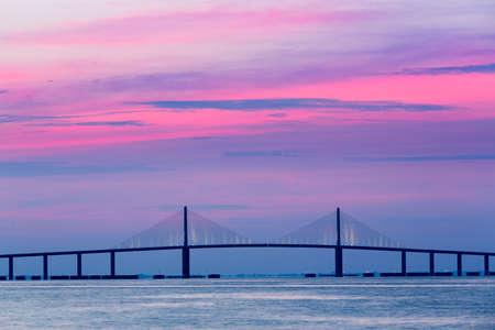 Brilliant sunrise svítí na obloze za Sunshine Skyway Bridge od St Petersburg na Floridě přes Tampa Bay.