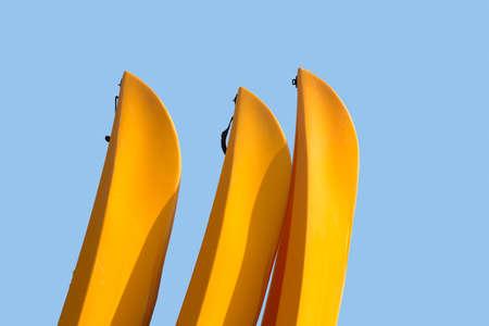 piragua: Tres proas amarillas de canoas o kayak con trazado de recorte para permitir el aislamiento de fácil desde el cielo azul detrás de los barcos