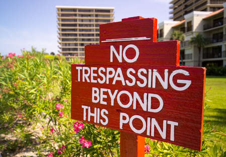 tresspass: Large no trespassing sign in front of flower gardens in holiday resort or private apartments by beach in Florida