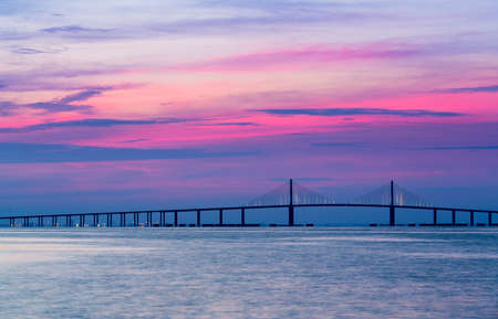 Panorama of bright sunrise lighting up the sky behind Sunshine Skyway Bridge from St Petersburg Florida across Tampa Bay.