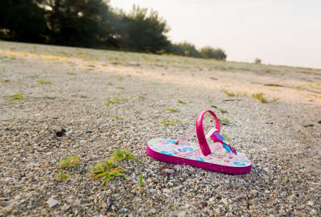 Concept image of the threat for child kidnapping or Amber alert with a single toddlers sandal alone on large beach with no sign of anyone Stock Photo