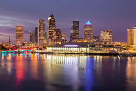 Florida skyline at Tampa with the Convention Center on the riverbank. Sun is just setting at dusk giving a fiery glow to the night sky. Editorial