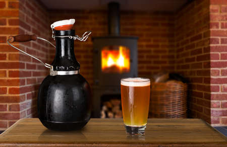 jarra de cerveza: Large 64 fl oz botella de cuatro growler pinta con un vaso de cerveza fría o cerveza en frente de fuego. Utilizado por microcervecerías para servir cerveza para consumo en el hogar Foto de archivo
