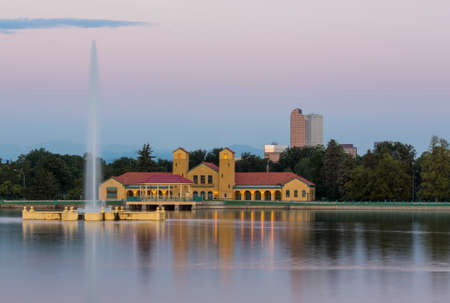 denver skyline at sunrise: Fountain and Boathouse at Ferril Lake with the city skyline of Denver Colorado in background just before sunrise