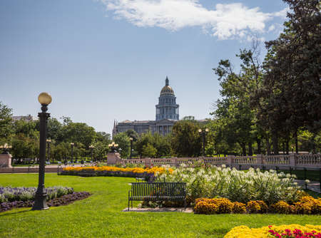capital of colorado: Flower beds and gardens of Civic Center Park with the gold leaf covered dome of State Capitol of Colorado in background Stock Photo