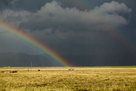 forbidding: Sun illuminating prairie grassland with dark and forbidding thunderclouds and downpour with van riding along lonely country road and rainbow ending over the vehicle Stock Photo