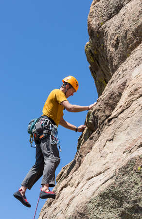 Senior male climber well equipped with cams and caribiners climbing on Turtle Rocks near Buena Vista Colorado photo