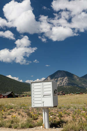 american field service: Metal mailbox container for rural homes and properties by mountains of Colorado Stock Photo