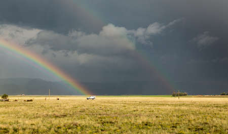 Sun illuminating prairie grassland with dark and forbidding thunderclouds and downpour with van riding along lonely country road and rainbow ending over the vehicle Banque d'images