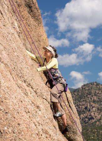 tenacious: Senior female climber on rope assisted climb on Turtle Rocks near Buena Vista Colorado