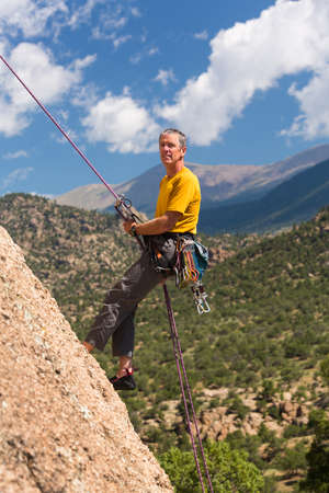 well equipped: Senior male climber well equipped with cams and caribiners rappelling down Turtle Rocks near Buena Vista Colorado Stock Photo