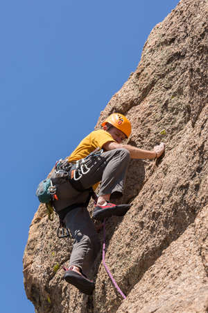 well equipped: Senior male climber well equipped with cams and caribiners climbing on Turtle Rocks near Buena Vista Colorado Stock Photo