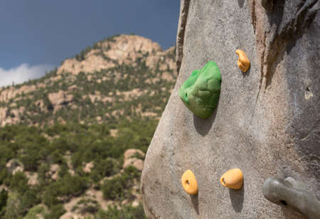bolted: Climbing wall with hand holds and bolted fasteners with real mountain and rocks in the background