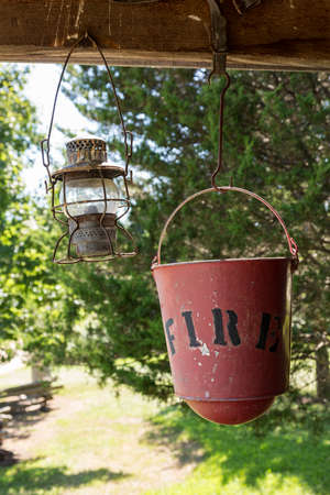 rafters: Old worn fire bucket and oil lamp hanging from rafters of log cabin Stock Photo