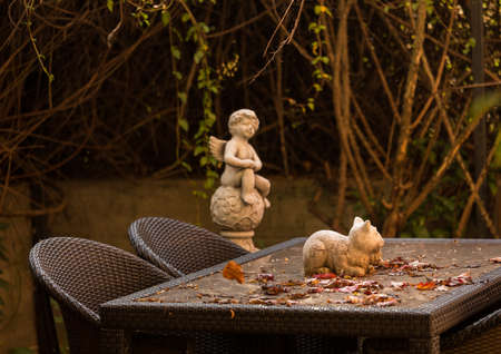 angel cat: Warm colors of rustic autumn garden table with falling leaves and statue of cat and angel in background