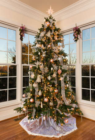 ornately: Ornately decorated and lit Christmas tree in the corner of a modern family home with trees lit by setting sun Stock Photo