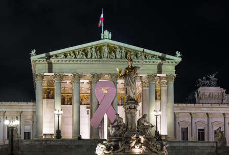 Illuminated facade of Austrian Parliament building with pink cancer ribbon in Vienna, Austria photo