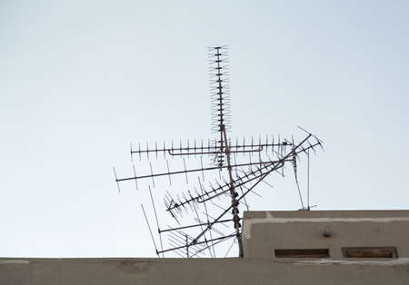 the antennae: Confused set of TV aerials or antennae pointing in many directions on rooftop