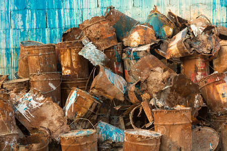 Stack or pile of old rusty metal paint cans with blue and white paint running from the stack