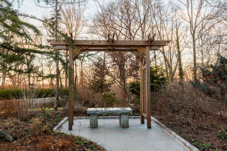 arbor: Polished granite seat under a wooden arbor or gazebo in woods at sunset in winter