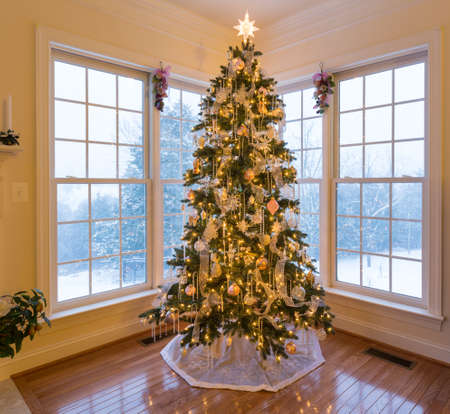 snow tree: Christmas tree in modern home with snow falling outside the windows on the trees and garden