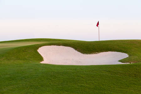 hawaii flag: Red flag of golf hole above sand trap or bunker on beautiful course at sunset Stock Photo