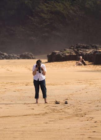 taking photo: Senior caucasian woman taking photo of the beach with camera