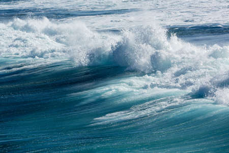 turbulence: Frozen motion of large wave or breaker approaching shore and short shutter speed freezing the water into droplets Stock Photo