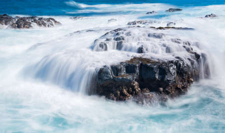 swell: Strong sea waves flow over lava rocks on edge of the shore near Queens Bath, Kauai, Hawaii Stock Photo