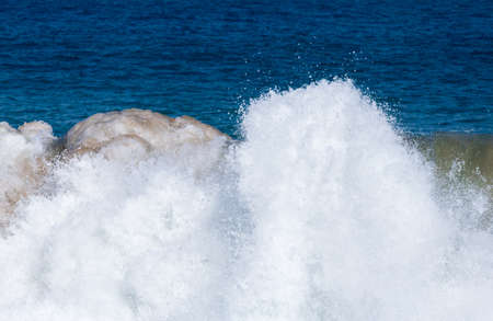 short wave: Frozen motion of large wave or breaker approaching shore and short shutter speed freezing the water into droplets Stock Photo