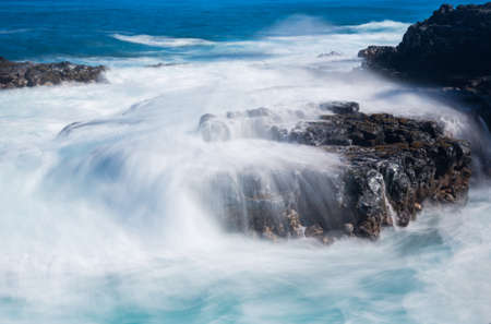 Strong sea waves flow over lava rocks on edge of the shore near Queens Bath, Kauai, Hawaii Stock Photo