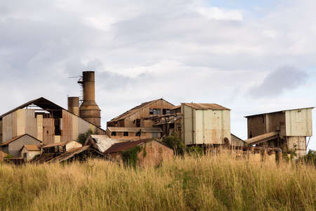 abandoned factory: Close view of old deserted sugar mill being overgrown by nature near Koloa, Kauai in Hawaii