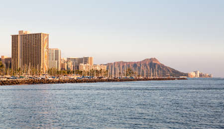 diamond head: Panorama of the skyline of Waikiki at sunset or dusk with yachts and boats in Ala Moana harbor and Hilton Hawaiian Village framing Diamond Head in Waikiki, Oahu, Hawaii