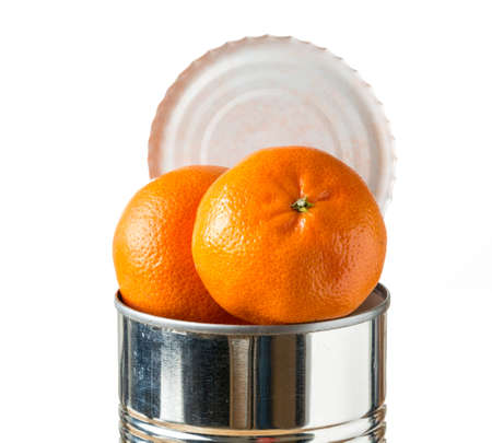 heaped: Orange, tangerine or satsuma fruit heaped inside opened tin can container in concept of fresh food coming in cans