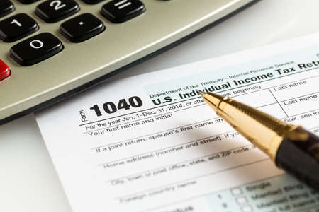 Usa Tax Form 1040 For Year 2014 With A Pen And Calculator