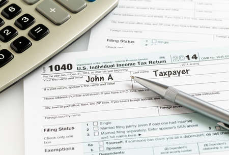 irs: USA tax form 1040 for year 2014 with a pen and calculator illustrating completion of tax forms for the IRS