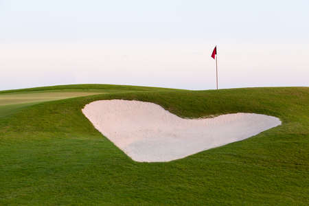 Heart shaped sand bunker in front of red flag of golf hole on beautiful course at sunset illustrating love for game of golf Фото со стока