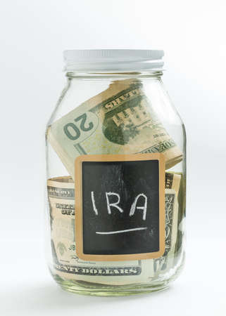 Glass jar on white background with black chalk label or panel and used for saving of US dollar bills for IRA and retirement