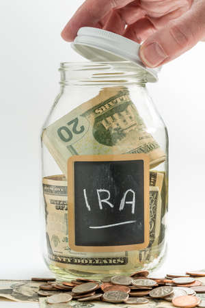 Hand opening lid of glass jar on white background with black chalk label and used for savings US dollar bills for IRA and retirement