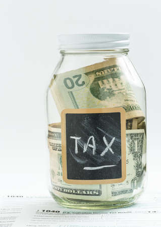 Glass jar on white background with black chalk label or panel and used for saving US dollar bills for income tax