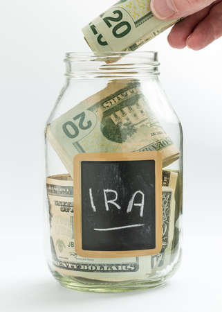 ira: Caucasian hand putting money into glass jar on white background with black chalk label and used for savings US dollar bills for retirement