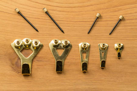 five objects: Set of five different sized brass picture hooks and nails or pins against a wood background Stock Photo