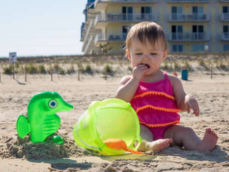 oc: Cute caucasian baby girl on sandy beach tasting sand for the first time in Ocean CIty, Maryland, USA