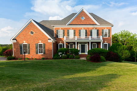 Front of home and garage of large single family modern US house with landscaped gardens and lawn on a warm sunny summers day Foto de archivo