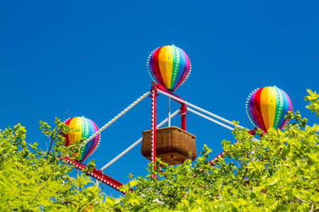 oc: Colorful lighted balloon shapes above baskets on childrens fairground ferris wheel