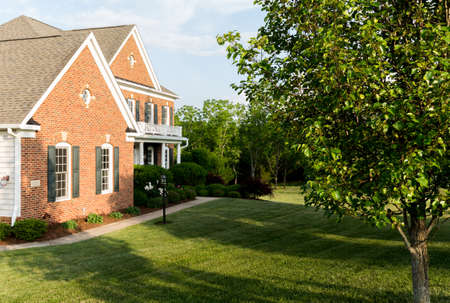 suburbs: Front of home and garage of large single family modern US house with landscaped gardens and lawn on a warm sunny summers day Stock Photo